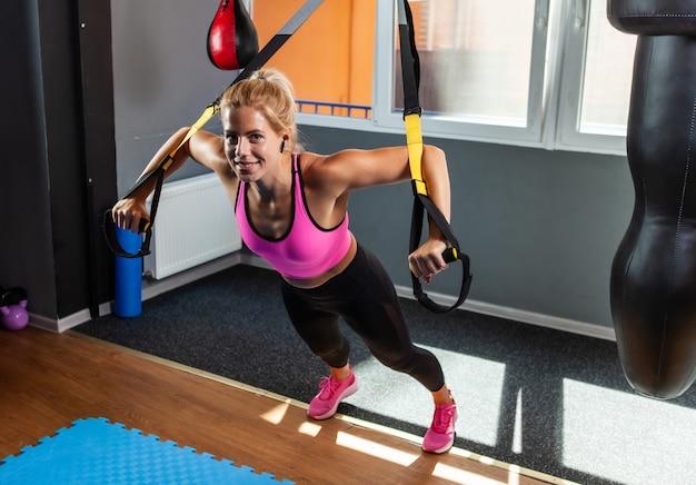 ジムでフィットネスtrxストラップを使ってエクササイズをしている若いブロンドの女性にフィットします。女性の体のためのフィットネストレーニング
