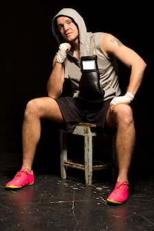 Fit young boxer sitting waiting for a fight on a wooden stool