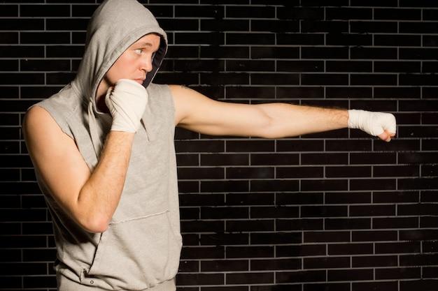 맞는 젊은 권투 선수는 펀치를 던지고 운동