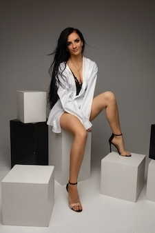 Montare una giovane donna bruna che indossa una camicia con gambe nude sedute su cubi bianchi e neri su sfondo grigio, copia spazio. foto di alta qualità