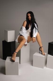 灰色の背景、コピースペースの黒と白の立方体に座っている裸の足でシャツを着ている若いブルネットの女性に合います。高品質の写真