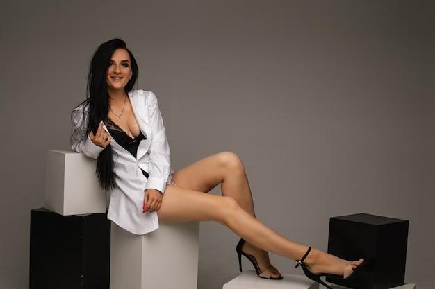 Подходит молодая брюнетка женщина в рубашке с голыми ногами, сидя на черно-белых кубах на сером фоне, копией пространства. фото высокого качества