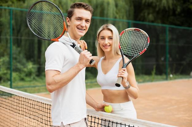 Подходит молодая пара готова играть в теннис