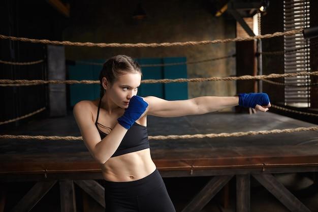 Giovane pugile femminile in forma con un corpo muscoloso perfetto che padroneggia le tecniche di punzonatura in palestra, si concentra sul processo, allunga la mano e guarda davanti a lei