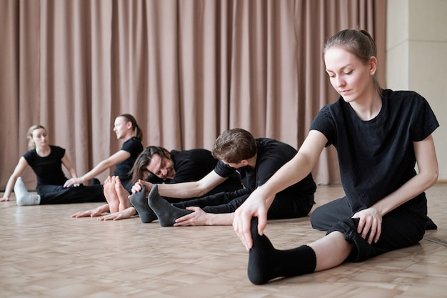 Fit young female dancer stretching one leg while sitting on the floor during training
