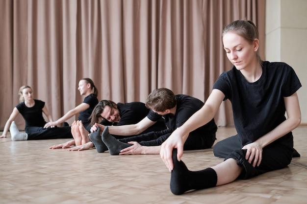 Подходит молодой танцовщице, растягивая одну ногу, сидя на полу во время тренировки