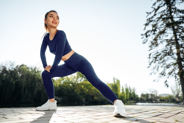Fit young girl in dark blue sportswear exercising in park