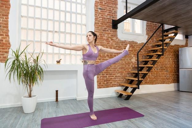 家庭でのトレーニングの練習をしている若い女の子に合います。ヨガ、ピラティス、健康的なライフスタイル。テキスト用のスペース。