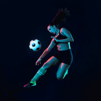 Fit young girl kicking soccer ball