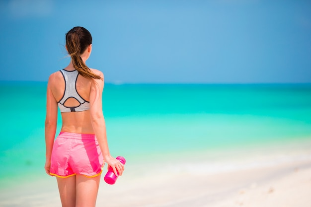 Fit young girl with bottle of water on white beach