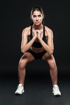 Подходящая молодая девушка тренируется, делая приседания с поднятыми руками, изолированную на черной стене