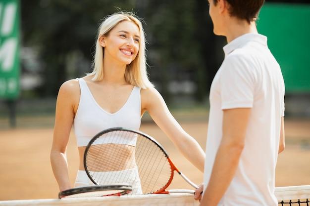 Подходит молодой мужчина и женщина, играя в теннис
