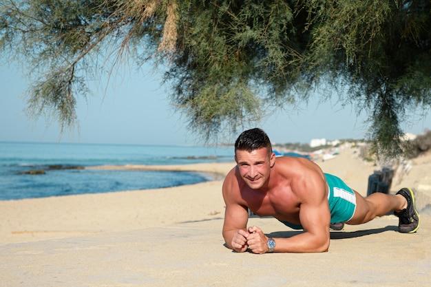 夏の日にビーチでコアトレーニングを行う若い男に合う