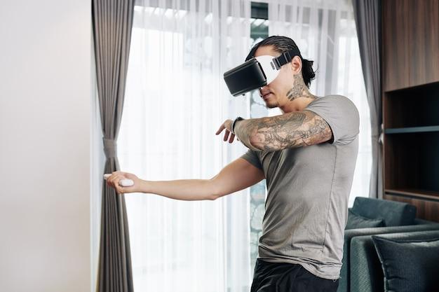 집에서 비디오 게임을 하는 가상 현실 헤드셋에 맞는 젊은 남자