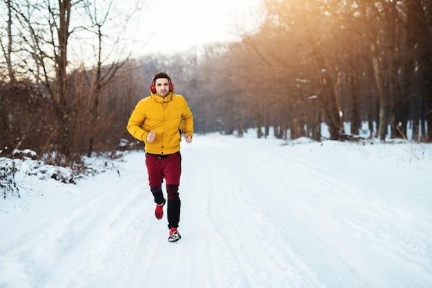 雪に覆われた冬の道で実行されているヘッドフォンで冬のスポーツウェアの若い男に合う