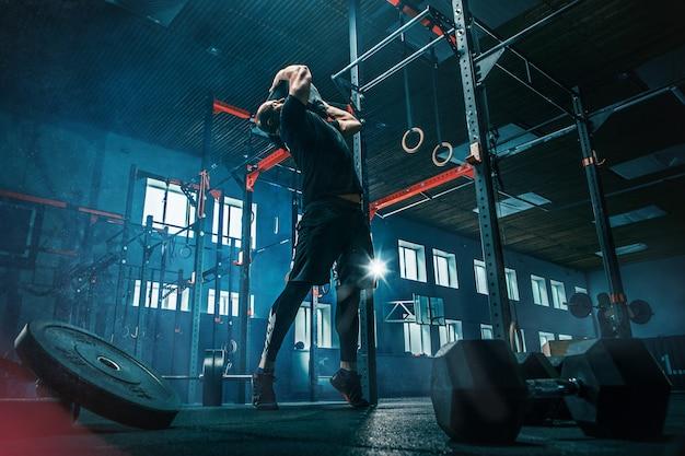 ジムで運動しているバーベルを持ち上げる若い男に合います。スポーツ、フィットネス、ウェイトリフティング、ボディービル、トレーニング、アスリート、トレーニングエクササイズのコンセプト