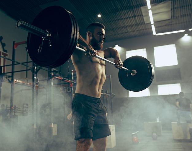 Штанги подходящего молодого человека поднимаясь разрабатывая в спортзале
