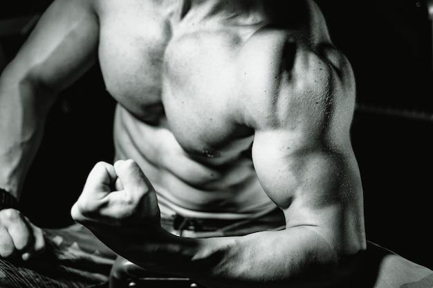 ジムで筋肉をポンピングする若い男に合います。スポーツ、フィットネス、ウェイトリフティング、ボディービル、トレーニング、アスリート、トレーニングエクササイズのコンセプト。横から見る