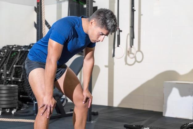 Молодой человек потеет после тренировки в тренажерном зале