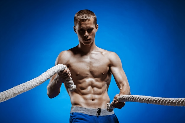 Подходит молодой человек с красивым торсом и веревкой на синем