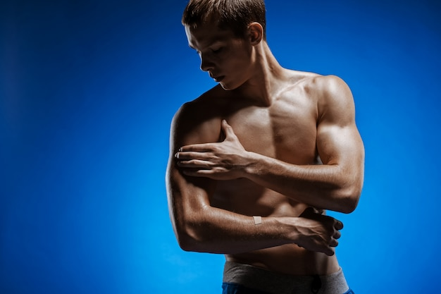 Fit young man with beautiful torso on blue wall