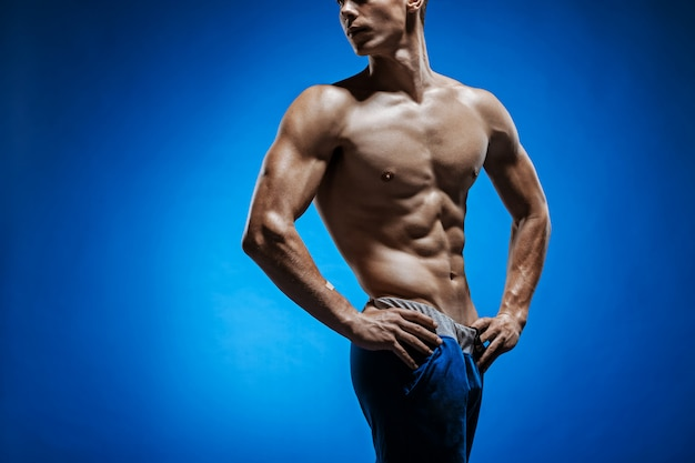 Fit young man with beautiful torso on blue