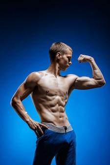 水色の壁に美しい胴体を持つ若い男に合う