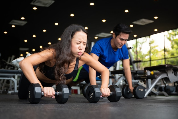 Fit young man and woman doing pushing up in a gym