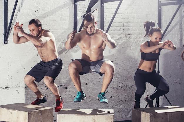 Подходящие молодые люди, делающие прыжки в коробку группой в тренажерном зале