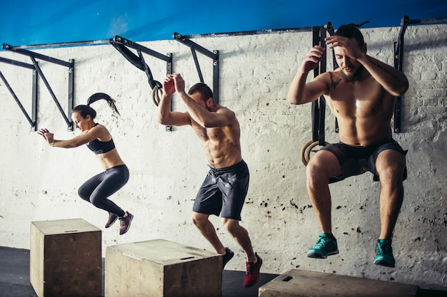 Fit young people doing box jumps as a group in a gym