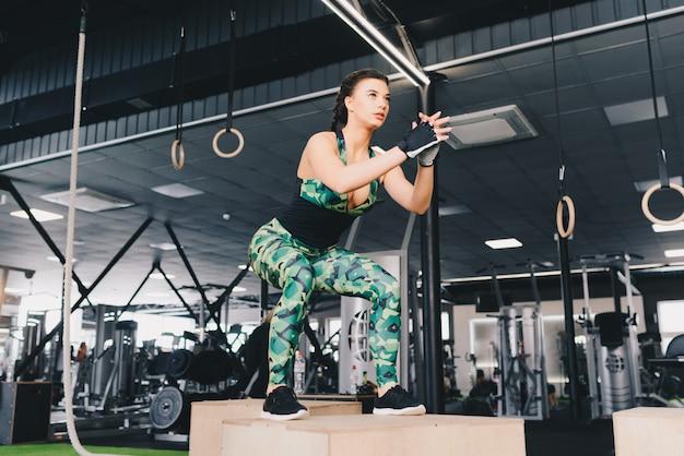 Crossfitスタイルのジムでジャンプ若いセクシーな女性ボックスに合います。女性アスリートはジムでボックスジャンプを行っています。