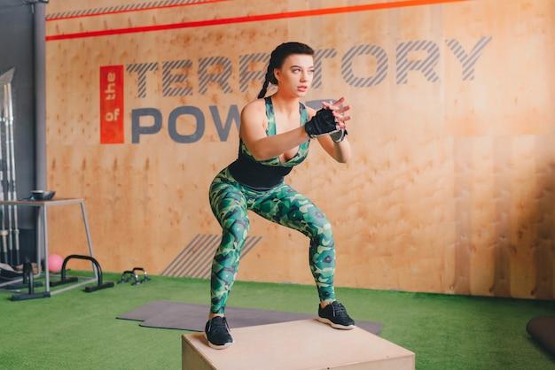 Crossfitスタイルのジムでジャンプ若い女性ボックスに合います。女性アスリートはジムでボックスジャンプを行っています。
