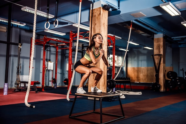 Fit young woman box jumping at a crossfit style