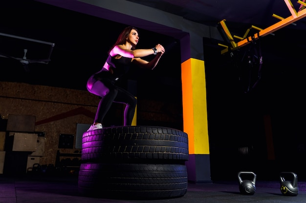 Fit young woman box jumping on tires