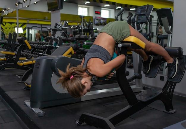 체육관에서 트레이너 백 머신에서 운동을 하는 젊은 여성에게 적합합니다. 보디 빌딩 및 피트니스