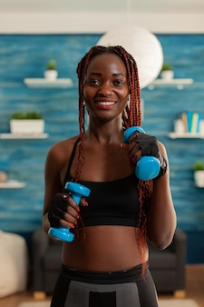 Fit young woman exercising biceps with dumbbells in home living room, dressed in sportwear