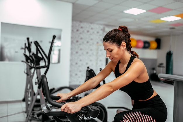 Fit young woman exercising on gym bike.