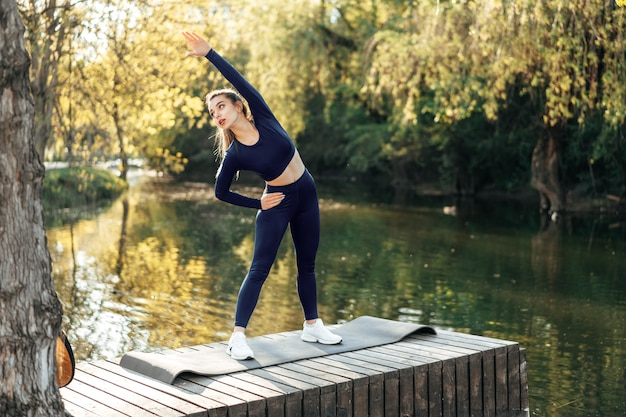 Fit young woman exercising on mat in the park