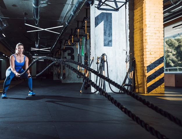 Fit young woman exercising with battle ropes