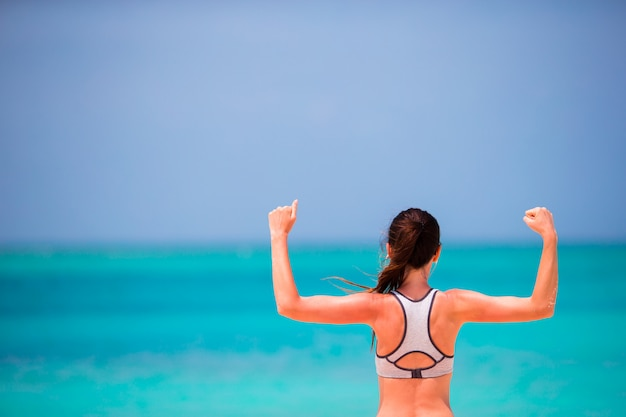 Fit young woman in her sportswear on the beach