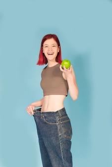 Подходит молодая женщина, держащая зеленое яблоко и в больших брюках