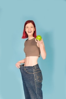Fit young woman holding green apple and wearing big pants
