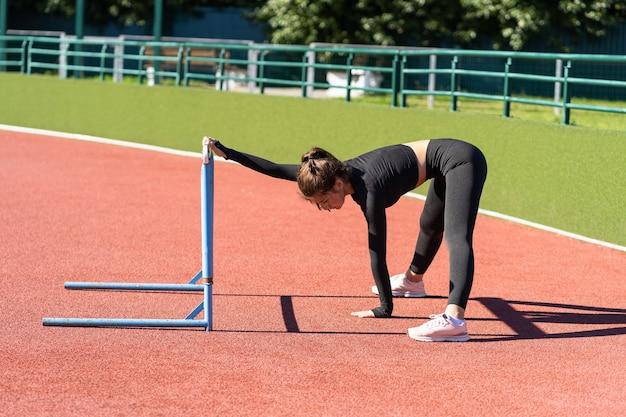 晴れた夏の日にトレッドミルのゴム製スタジアムで走る前に、筋力トレーニングをしている黒いスポーツウェアに若い女性を合わせてください