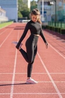 ファンクショナルトレーニングを行う筋肉を伸ばす黒いスポーツウェアに若い女性をフィットさせる
