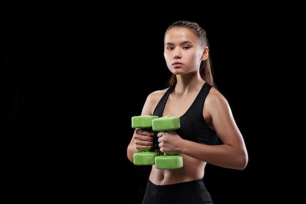 Подходит для молодой женщины в спортивной одежде, держащей гантели на груди во время упражнения у черной стены