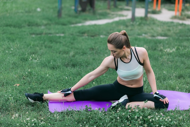 Подходящая молодая женщина в спортивной одежде выполняет растягивание после тренировки снаружи