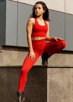 Подходит молодая женщина в спортивной одежде позирует