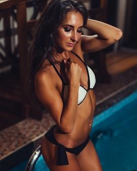 Подходящая молодая женщина в купальных костюмах готовя бассейн