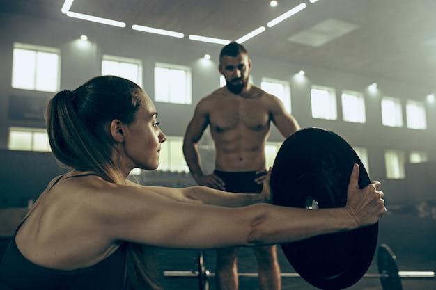 ジムで運動しているバーベルを持ち上げる若い女性に合います。スポーツ、フィットネス、ウェイトリフティング、ボディービル、トレーニング、アスリート、トレーニングエクササイズのコンセプト