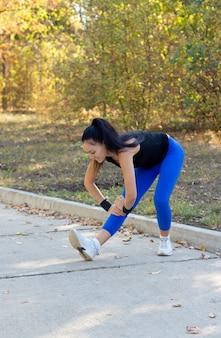 公園を通るタール道路でトレーニングを開始する前に、筋肉を伸ばして腰を下ろしている若い女性にフィットします